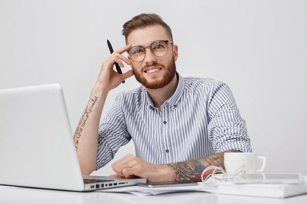 Foto van doordachte getatoeëerde mannelijke ondernemer met dikke baard en trendy kapsel begint 's ochtends te werken
