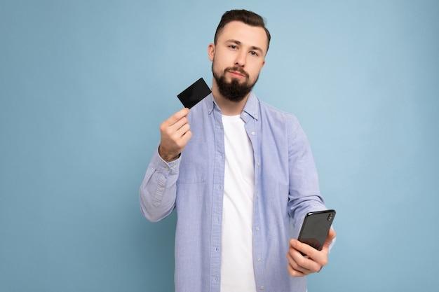 Foto van doordachte knappe aantrekkelijke donkerbruine ongeschoren jonge man met casual blauw shirt en