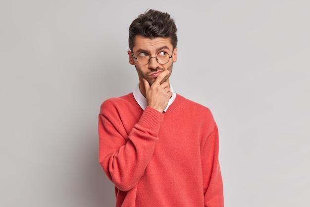 Foto van doordachte knappe volwassen europese man houdt kin en kijkt peinzend weg probeert probleem op te lossen