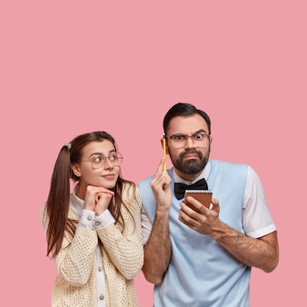 Foto van doordachte man met dikke haren, houdt notitieblok en potlood vast, denkt na over ideeën voor het schrijven van een essay, zijn vriendin geek probeert te helpen, dicht bij elkaar te staan, samen te werken, geïsoleerd op roze