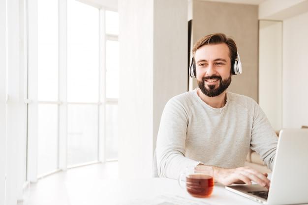Foto van doordachte man met kort bruin haar en baard, luisteren naar muziek via draadloze hoofdtelefoons en chatten op notebook