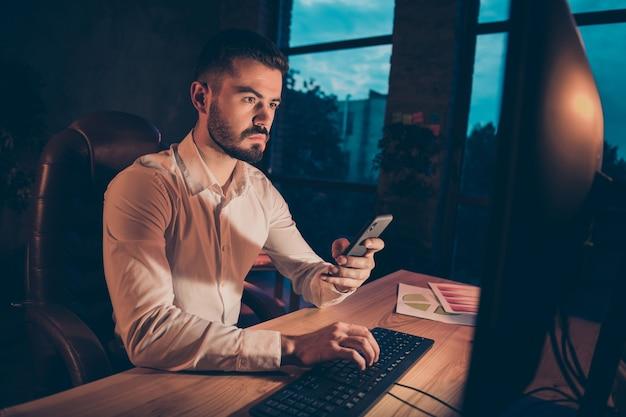 Foto van doordachte serieuze man die door zijn telefoon bladert