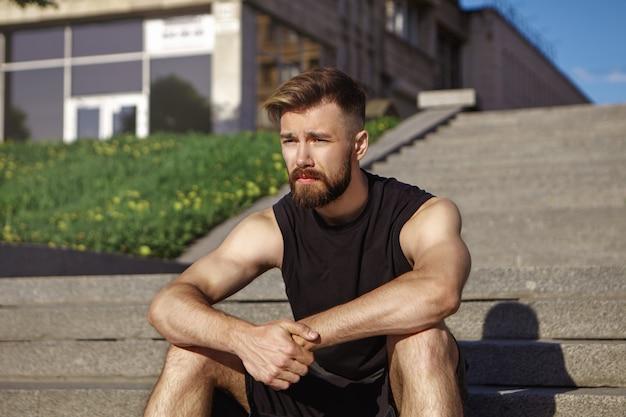 Foto van doordachte uitgeputte jonge mannelijke atleet met pluizige baard en gebruinde huid zittend op betonnen treden, ontspannen na intensieve cardiotraining sport, fitness, stijl en mode-concept