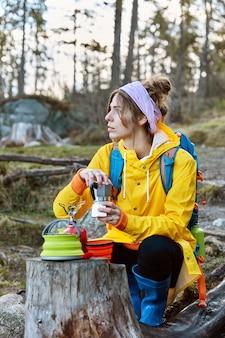 Foto van doordachte vrouw heeft koffie op een schilderachtige plek, poseert in de buurt van stempel met draagbare kampeerfornuis en koffiezetapparaat