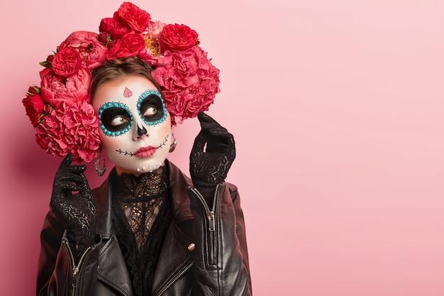 Foto van doordachte vrouw met halloween-make-up, gekleed in zwarte traditionele outfit