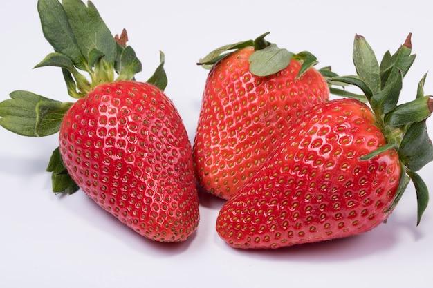 Foto van drie verse rode aardbeien met aardbeiblad dat op witte oppervlakte wordt geïsoleerd