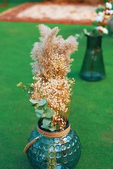 Foto van droge bloemen in een blauwe vaas voor decoratie