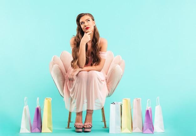 Foto van dromen vrouw 20s in jurk zittend op roze fauteuil en denken na het winkelen met veel kleurrijke tassen, geïsoleerd over blauwe muur