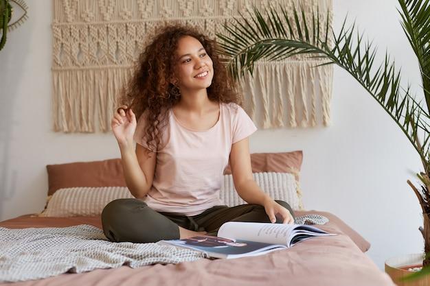 Foto van dromerig jonge afro-amerikaanse vrouw met krullend haar, zit op het bed en kijkt weg, glimlacht en leest een nieuw reismagazine.