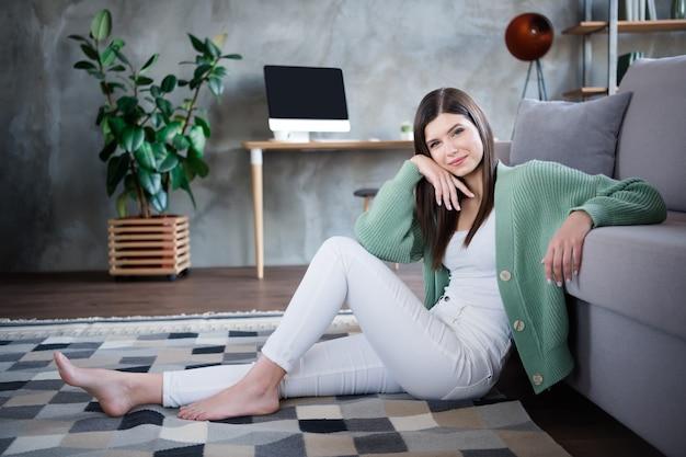 Foto van dromerig meisje zit op de vloer in een appartement studio huis