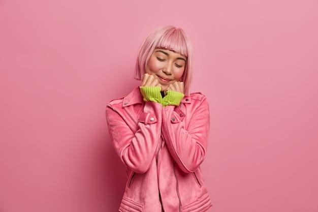 Foto van dromerige aziatische vrouw houdt de handen onder de kin, sluit de ogen en lacht zachtjes, dagdroomt en stelt zich iets aangenaams voor