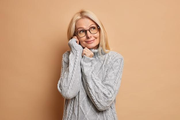 Foto van dromerige blonde vrouw houdt handen in de buurt van gezicht en denkt aan iets aangenaams geconcentreerd weg glimlacht zachtjes gekleed in grijze casual jumper optische bril. gezichtsuitdrukkingen concept
