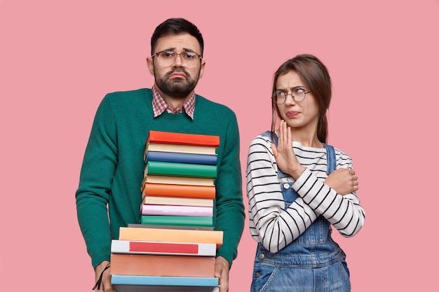 Foto van drukke bebaarde mannelijke student draagt veel boeken, ontevreden vrouw toont onenigheid gebaar