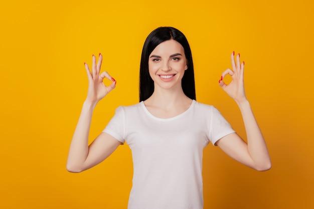 Foto van een aantrekkelijk vrolijk jong meisje dat een goed teken-advertentieoplossing toont, geïsoleerd over een felgele kleurachtergrond