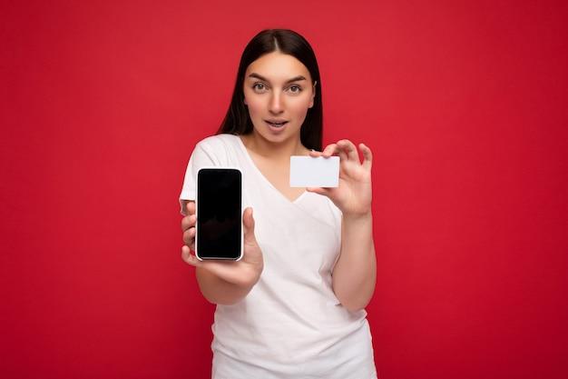 Foto van een aantrekkelijke, gelukkige jonge brunette vrouw die een casual wit t-shirt draagt dat over rood wordt geïsoleerd