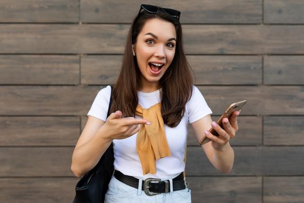 Foto van een aantrekkelijke, geschokte, verraste jonge vrouw die vrijetijdskleding draagt en op straat staat met de mobiele telefoon die naar de smartphone kijkt.