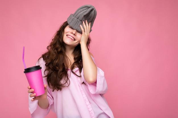 Foto van een aantrekkelijke jonge gelukkig lachende brunette vrouw die alledaagse stijlvolle kleding draagt, geïsoleerd over een kleurrijke achtergrondmuur met een papieren beker voor uitgesneden thee drinken en plezier maken. kopieer ruimte