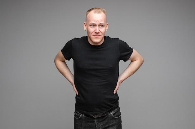 Foto van een aantrekkelijke man met een zwart t-shirt en een spijkerbroek poserend voor de camera met de handen aan een riem op een grijze achtergrond