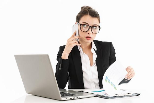 Foto van een aantrekkelijke vrouwelijke werkneemster, gekleed in formele kleding, zittend aan een bureau en werkend op een laptop op kantoor geïsoleerd over een witte muur