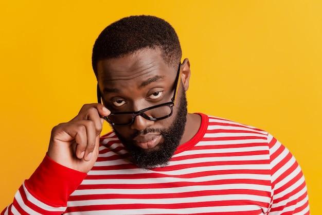 Foto van een afrikaanse man met een serieus gezicht opstijgen bril op gele achtergrond
