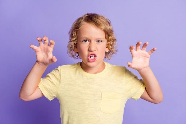 Foto van een angstaanjagende kleine jongen die in de camera kijkt en zijn klauwen opheft, geïsoleerd over een violette kleurachtergrond