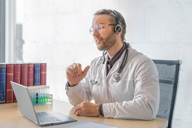 Foto van een arts van middelbare leeftijd tijdens een online consult met een patiënt. het concept van gezondheidszorg en moderne technologieën in de geneeskunde.