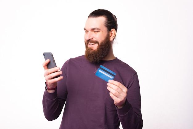 Foto van een bebaarde man die in zijn telefoon kijkt en een creditcard vasthoudt