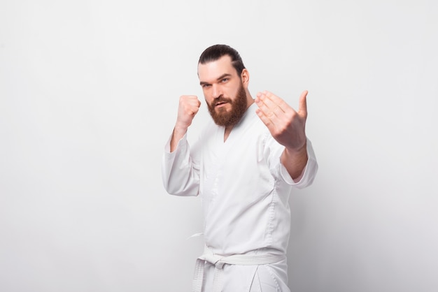 Foto van een bebaarde man in taekwondo-uniform gevecht voorbereiden, kom op