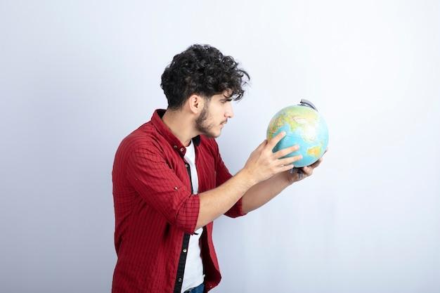 Foto van een bebaarde man met een wereldbol tegen een witte muur.
