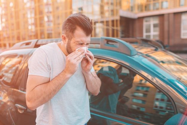 Foto van een bebaarde man met zakdoek. zieke man heeft loopneus. man maakt een remedie voor de verkoudheid