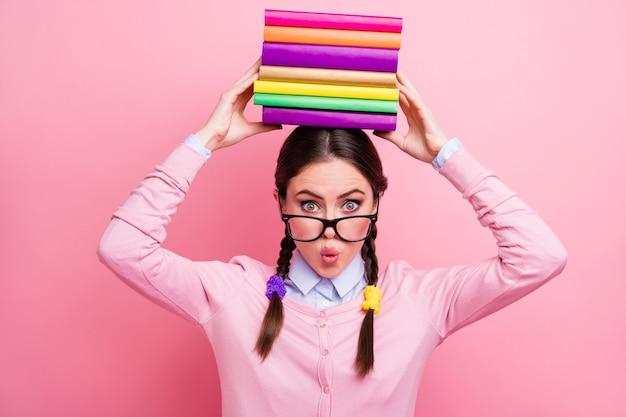 Foto van een behoorlijk geschokte student dame houdt boeken stapel op het hoofd voorbereiding van onderzoek college universiteit groot huiswerk overweldigd slijtage shirt pullover specificaties geïsoleerde roze kleur achtergrond