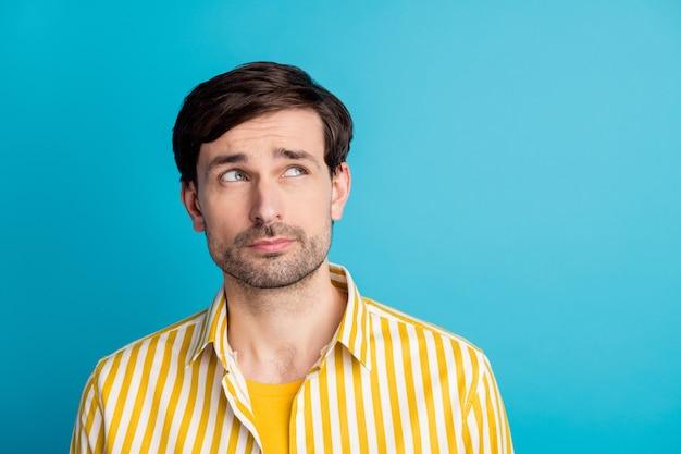 Foto van een bewuste onzekere man kijk copyspace denk gedachten probeer beslissen reis reis beslissing oplossing draag gestreept shirt geïsoleerd over blauwe kleur achtergrond
