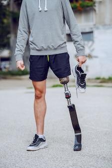 Foto van een blanke gehandicapte sportieve man uitgesneden die buiten met sneaker in de hand staat.