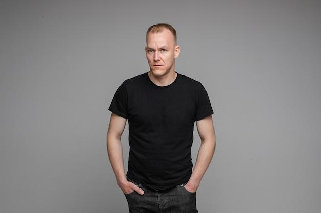 Foto van een blanke man houdt zijn handen in de zakken van zijn zwarte spijkerbroek en kijkt naar links geïsoleerd op een grijze achtergrond