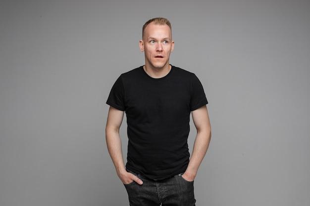 Foto van een blanke man houdt zijn handen in de zakken van zijn zwarte spijkerbroek en kijkt naar rechts geïsoleerd op een grijze achtergrond
