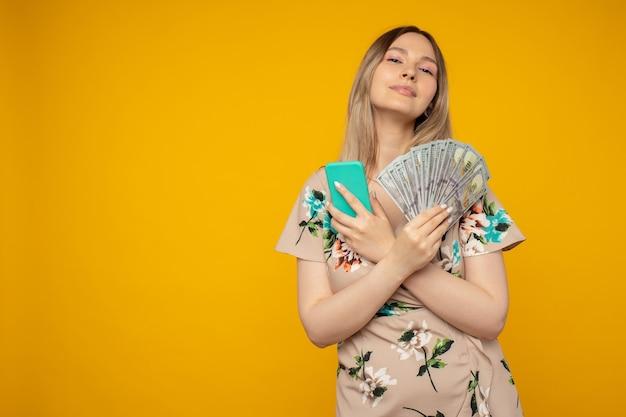 Foto van een blije gelukkige emotionele jonge vrouw die zich voordeed op een gele muurachtergrond met behulp van een mobiele telefoon die geld aanhoudt.