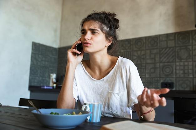 Foto van een broeierige brunette vrouw die een boek leest en op mobiel praat terwijl ze thuis ontbijt in de keuken