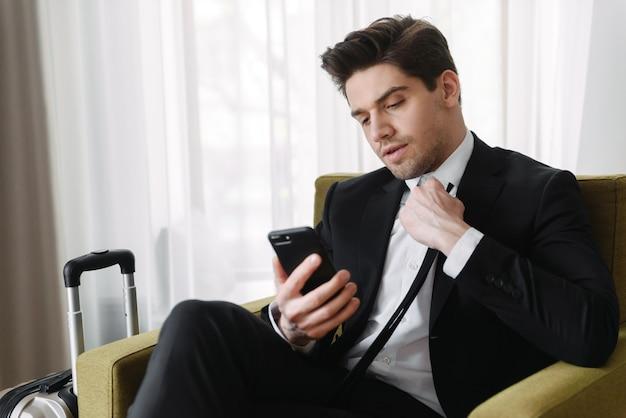 Foto van een broeierige brunette zakenman die een zwart pak draagt en op zijn mobiel typt terwijl hij op een fauteuil in een hotelappartement zit
