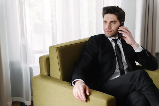 Foto van een broeierige, knappe zakenman in een zwart pak die op zijn mobiel praat terwijl hij op een fauteuil in een hotelappartement zit