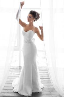 Foto van een bruid in een witte lange jurk met make-up en kapsel