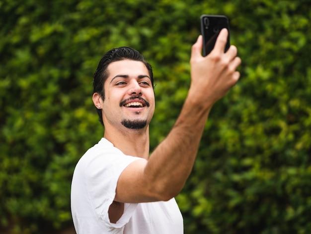 Foto van een brunette man die selfies neemt tegen een groen
