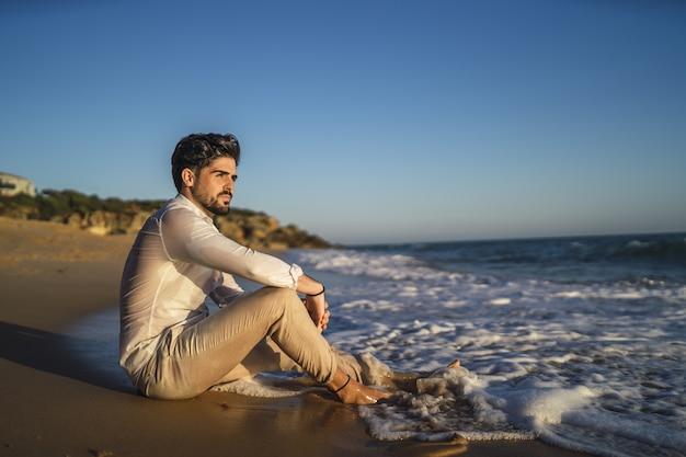 Foto van een brunette man zittend op het zand in een strand
