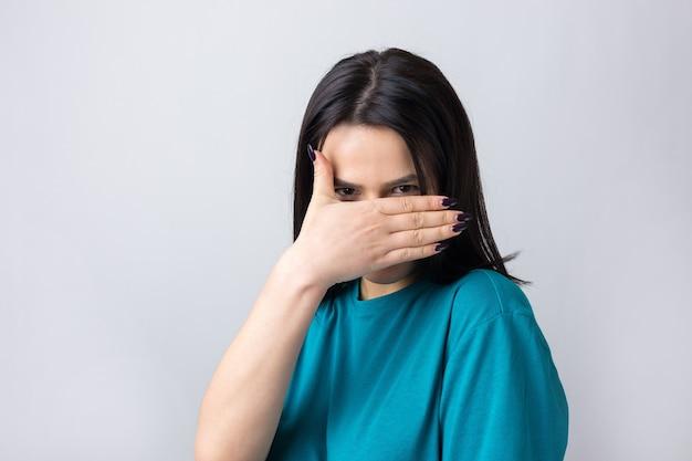 Foto van een brunette tienermeisje dat haar gezicht bedekt met handen en door haar vingers gluurt.