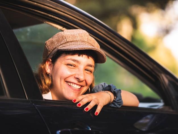 Foto van een brunette vrouw in een zwarte auto met een geweldige glimlach