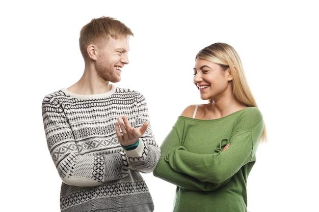 Foto van een charismatische man met stoppels die vrolijk lacht terwijl hij een grappig verhaal vertelt aan aantrekkelijke jonge vrouw met blond haar die om zijn grappen lacht. leuk paar praten