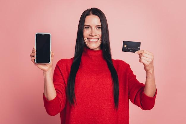 Foto van een charmante dame die een nieuw telefoonmodel vasthoudt dat contactloos een trui draagt, geïsoleerd op een roze achtergrond