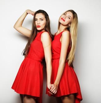Foto van een charmante jonge meisjes in een rode jurk op een witte achtergrond