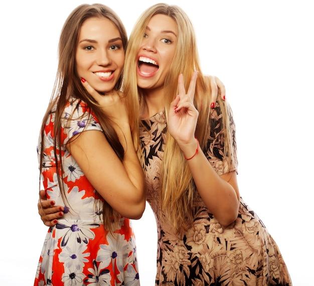 Foto van een charmante jonge meisjes vrienden in kleurrijke jurk op witte achtergrond