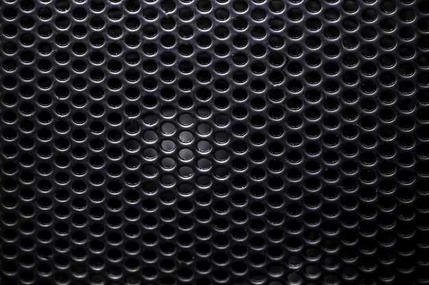 Foto van een close-up van een muzikale kolom verborgen achter een raster met een patroon van ritmisch gerangschikte gaten, achtergrondafbeelding