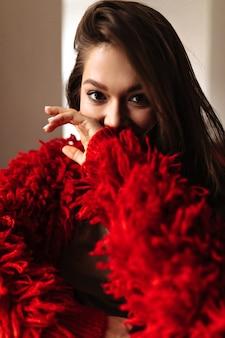 Foto van een dame in een rood jasje dat haar gezicht bedekt met haar hand. vrouw die met bruine ogen camera bekijkt.